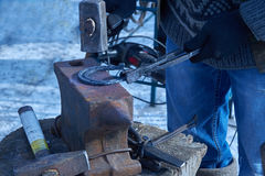 Blacksmith forges horseshoe on anvil. Blacksmith forges a horseshoe on the anvil Royalty Free Stock Photography