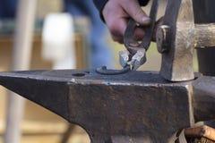 Blacksmith forges a horseshoe Royalty Free Stock Photo