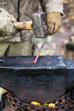 Blacksmith forges hot steel rod with sledgehammer Stock Images