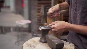 Blacksmith forges metal. Asian Street Craftman.