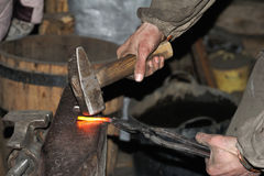 Blacksmith forges a red-hot metal hammer Royalty Free Stock Image