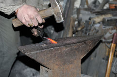 Blacksmith forges a red-hot metal hammer Stock Photography