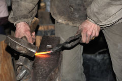Blacksmith forges a red-hot metal hammer Stock Photos