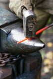 Blacksmith forges red hot steel rod on anvil Stock Images