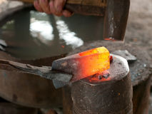 Blacksmith forging an ax Stock Image