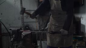 Blacksmith forging hot iron in a workshop