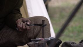 Blacksmith forging hot metal outdoors in his work shop. Craftsman hand forging metal outside.  stock video footage