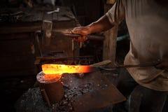 Blacksmith forging a knife Stock Photos