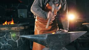 Blacksmith is forging metal in the workshop. HD stock footage