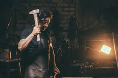 Blacksmith forging molten metal on the anvil in smithy. Stock Images