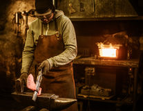 The blacksmith forging the molten metal on the anvil in smithy Stock Photography