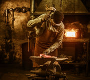 The blacksmith forging the molten metal on the anvil in smithy Royalty Free Stock Photo
