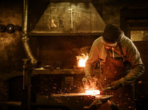 The blacksmith forging the molten metal on the anvil in smithy.  Stock Photos
