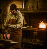 The blacksmith forging the molten metal on the anvil in smithy Royalty Free Stock Image