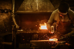 The blacksmith forging the molten metal on the anvil in smithy Stock Photo
