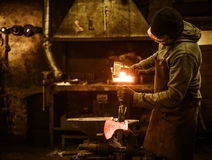 The blacksmith forging the molten metal on the anvil in smithy Royalty Free Stock Photos