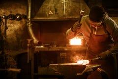Blacksmith forging the molten metal on the anvil in smithy Stock Photos