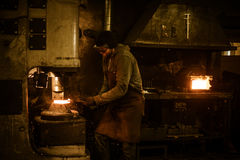Blacksmith forging the molten metal on the power hammer in smithy Royalty Free Stock Images