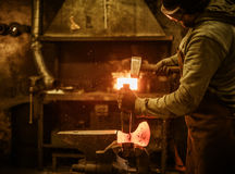 The blacksmith forging the molten metal on the rusty vise in smithy Stock Photos