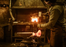 The blacksmith forging the molten metal on the rusty vise in smithy Royalty Free Stock Images