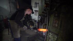 Blacksmith Forging Piece of Hot Iron Under Press