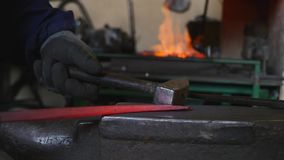 Blacksmith hammering the end of an Iron bar into a hook stock photos