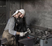 Blacksmith hammering a hot metal rod stock photography