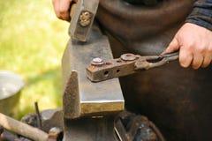 Blacksmith hammering hot steel. On anvil Royalty Free Stock Photos