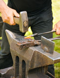 Blacksmith hammering hot steel. On anvil Royalty Free Stock Images