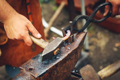 Blacksmith hammering a metal rod stock photography