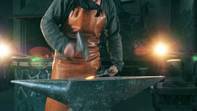 A blacksmith hammers a hot knife on anvil. 4K stock footage