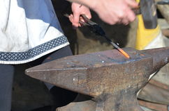 Blacksmith hammers red hot iron on an anvil Royalty Free Stock Images