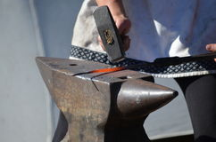 Blacksmith hammers red hot iron on an anvil Stock Image
