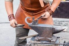 Blacksmith handles the horseshoe on the anvil Stock Photography
