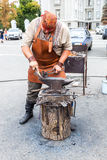 Blacksmith handles the horseshoe on the anvil at the outdoors Stock Photos