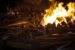 Blacksmith heating a metal rod Royalty Free Stock Photo