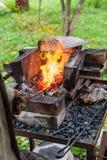 Blacksmith heats iron rod in forging furnace Royalty Free Stock Photo