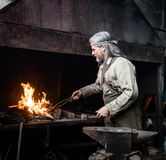 Blacksmith heats item before forging. focused on the fire Stock Images