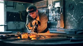 A blacksmith heats a knife on coal, holding it with tongs. 4K stock footage