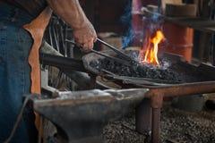 Blacksmith Heats Work in Fire Royalty Free Stock Photo