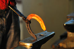 Blacksmith holding hot horseshoe Stock Photography