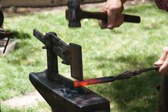 Blacksmith and hot iron. A blacksmith hammers a groove in a hot piece of iron using a special tool on his anvil in an outdoor shop Royalty Free Stock Photo