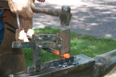Blacksmith and hot iron rod. A blacksmith shapes a groove in a hot rod of iron with a quickly moving hammer, using a special tool on his anvil Royalty Free Stock Photography