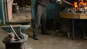 A blacksmith inverts the red-hot metal parts in the furnace, heat treatment, hardening and heating of metal, forge, slow stock footage