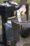 Blacksmith, ironsmith hitting hot steel. Black smith, ironsmith hitting hot steel on an anvil Royalty Free Stock Image