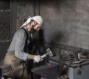 Blacksmith młotkuje gorącego metalu prącie fotografia stock