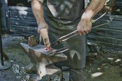 Blacksmith młotkuje, kuźnia podczas gdy żelazo jest gorący obraz stock