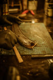 Blacksmith makes leather cover for axe Royalty Free Stock Images