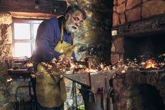 Blacksmith manually forging the molten metal on the anvil in. The blacksmith manually forging the molten metal on the anvil in smithy with spark fireworks stock image