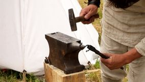 The blacksmith manually forging the molten metal on the anvil in smithy. stock footage